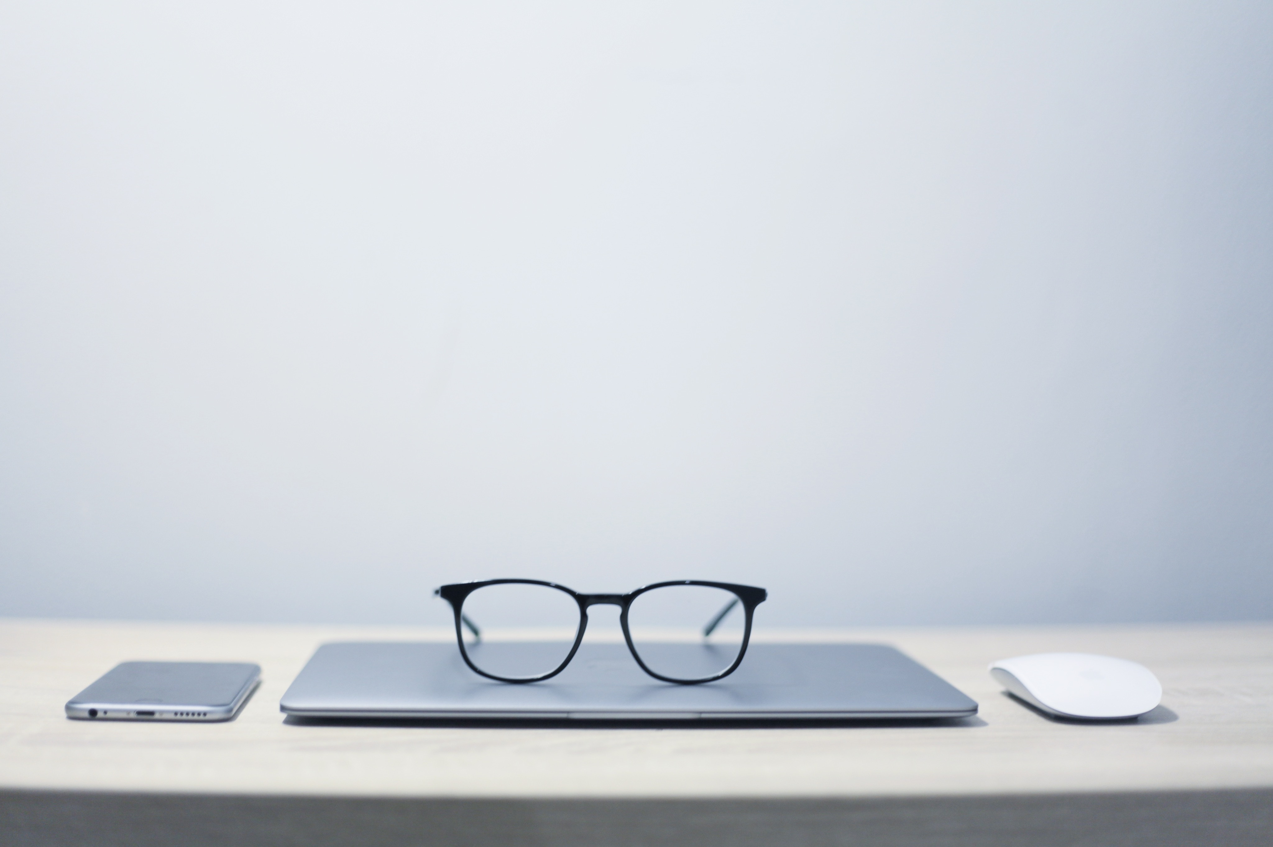 Image of close laptop with pair of glasses on top
