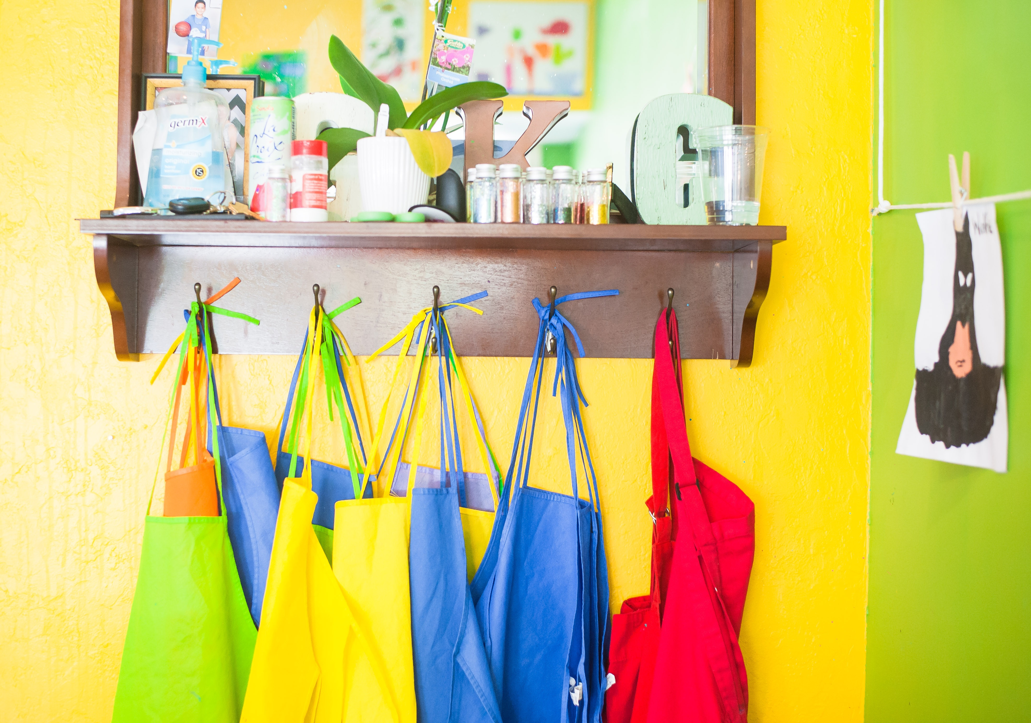 Brightly coloured aprons hang on yellow classroom wall