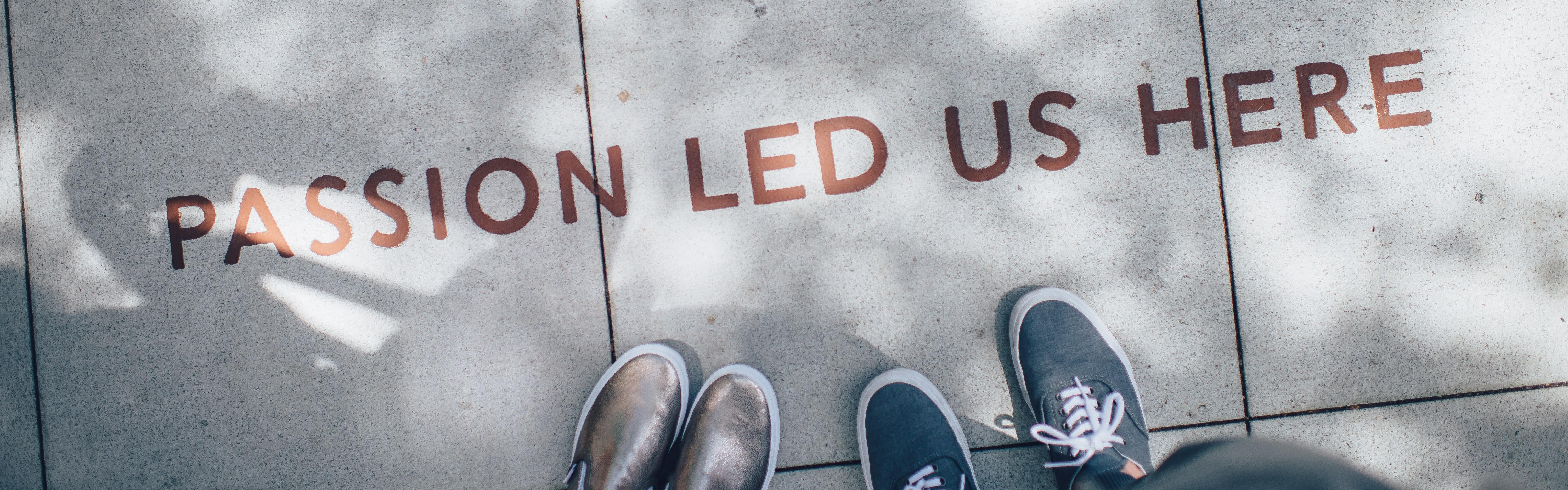 Photograph of two people's feet and concrete floor with slogan 'Passion led us here'