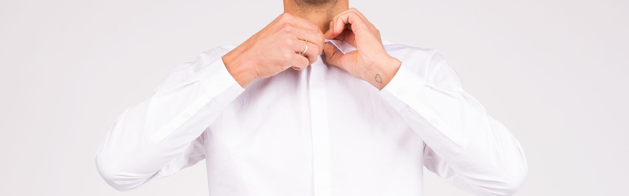 Man doing up collar of white shirt